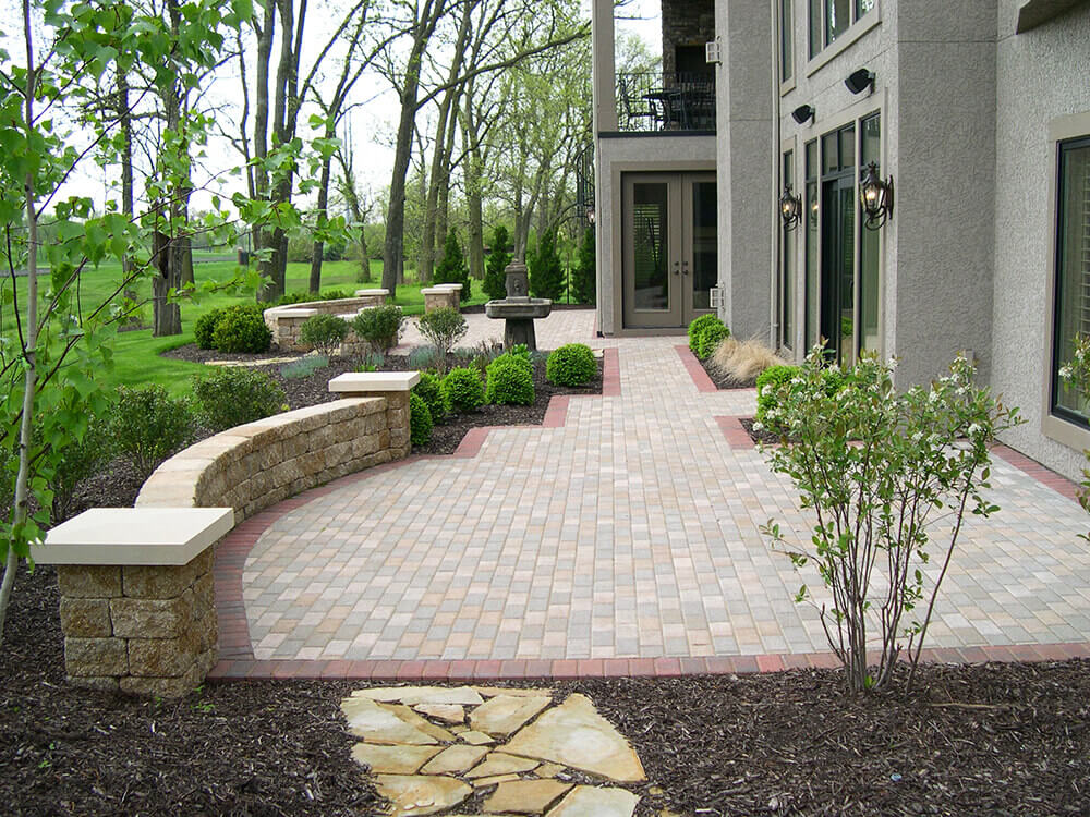 paved backyard with fountain and shrubs
