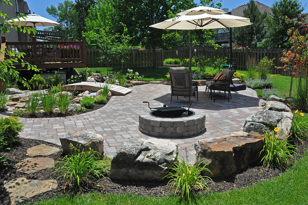 paved backyard with fire pit, seating area, and landscape design.