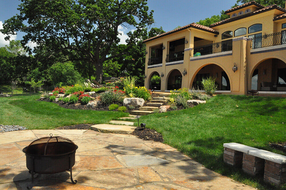 Residential landscape design with firepit and paved area.