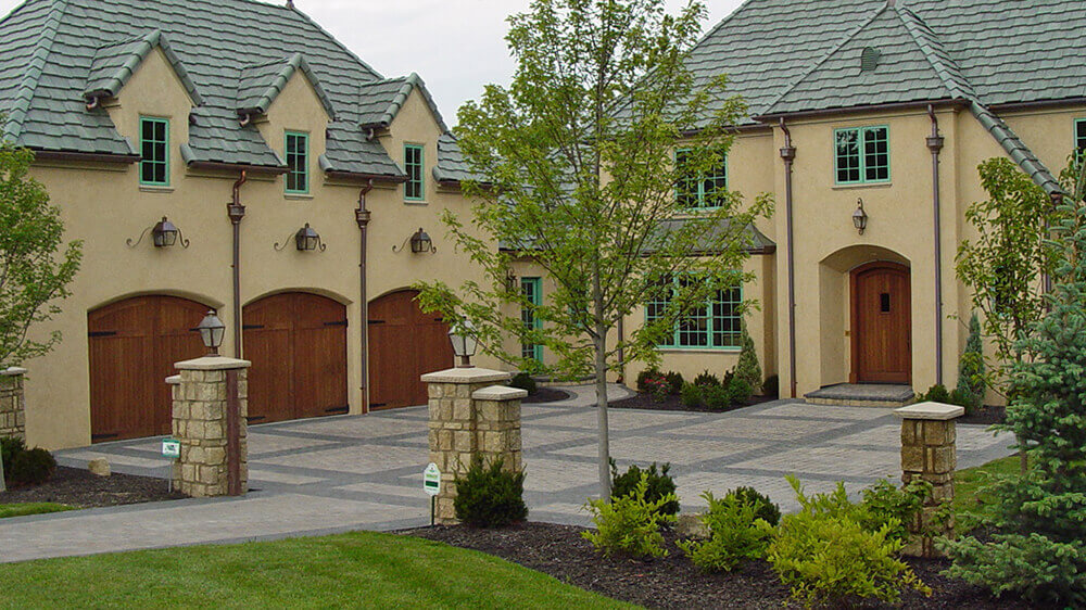 paved driveway with stone pillars and greenery