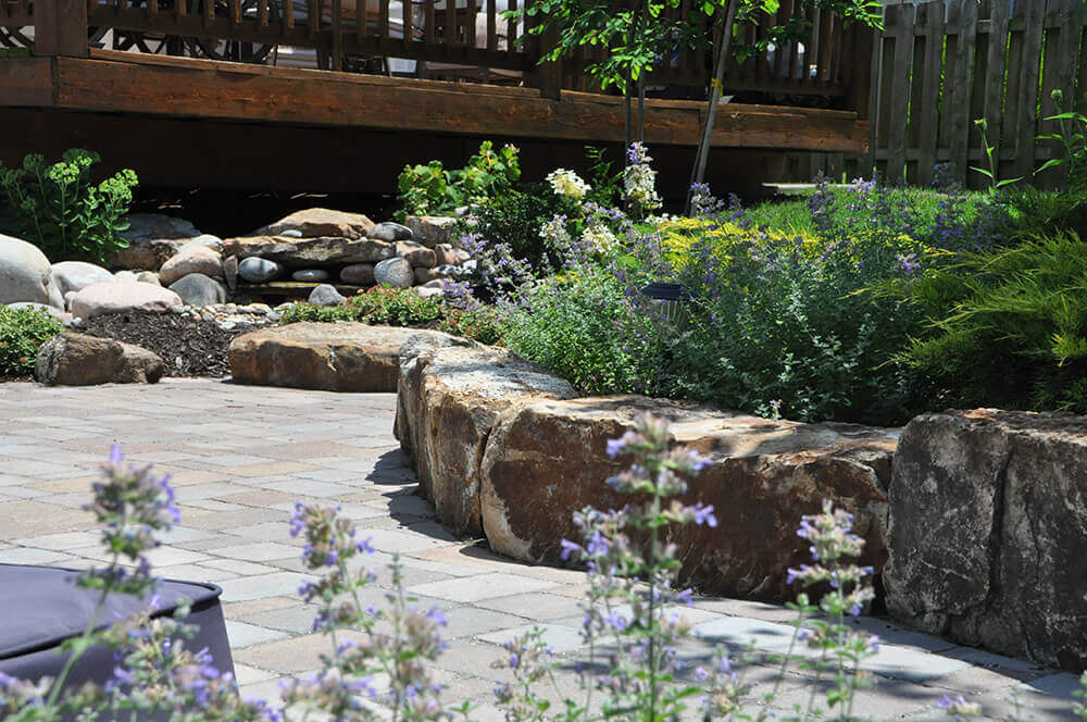 paved area with rocks and flowers