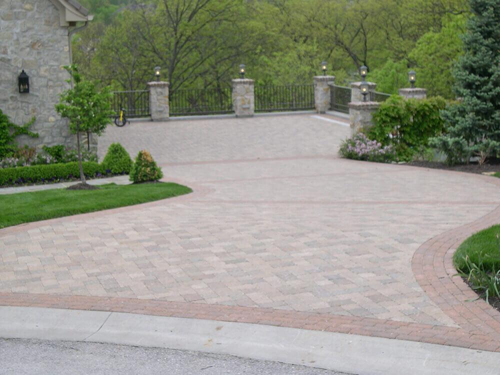 paved driveway with greenery