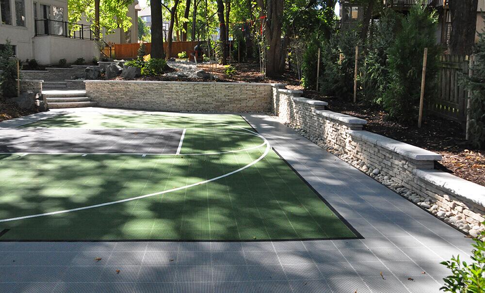 Backyard with paved area and basketball court.