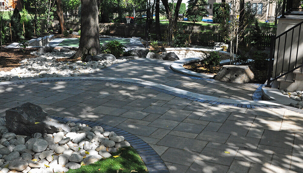 Paved area in backyard with basketball court.