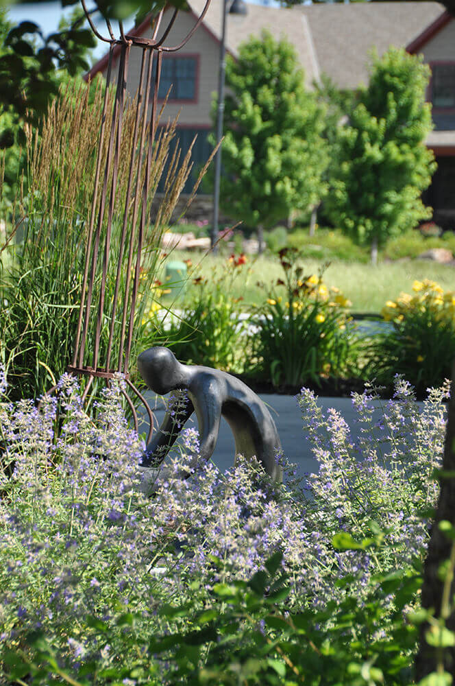 Small statue with bright flowers and greenery