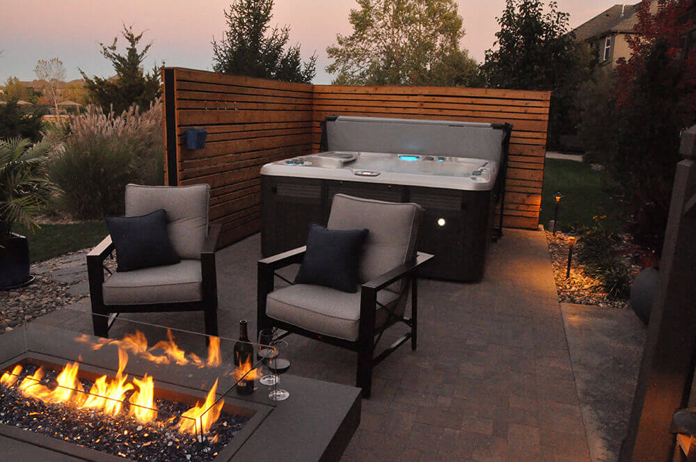 Backyard with hot tub and fire pit.