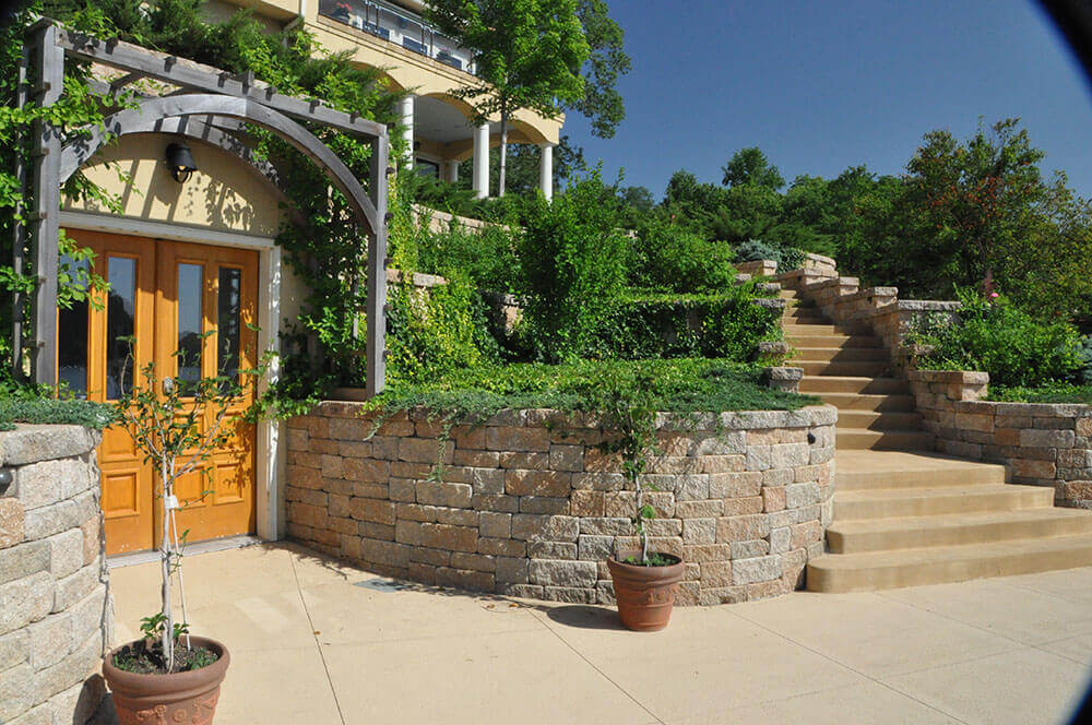 stone retaining wall with steps and hanging greenery