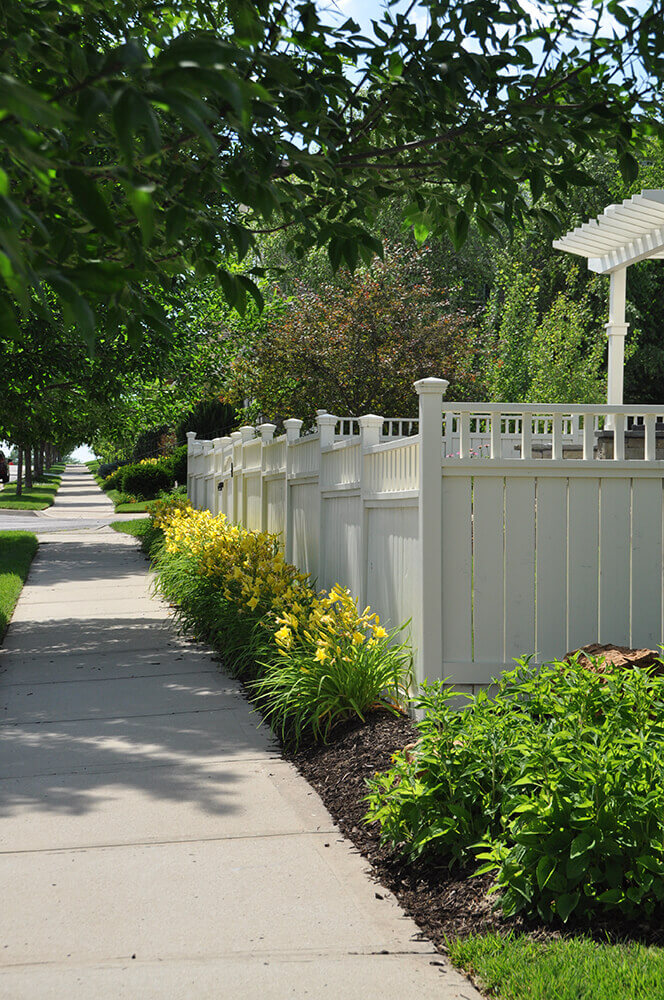 sidewalk with yellow flowers and white fence