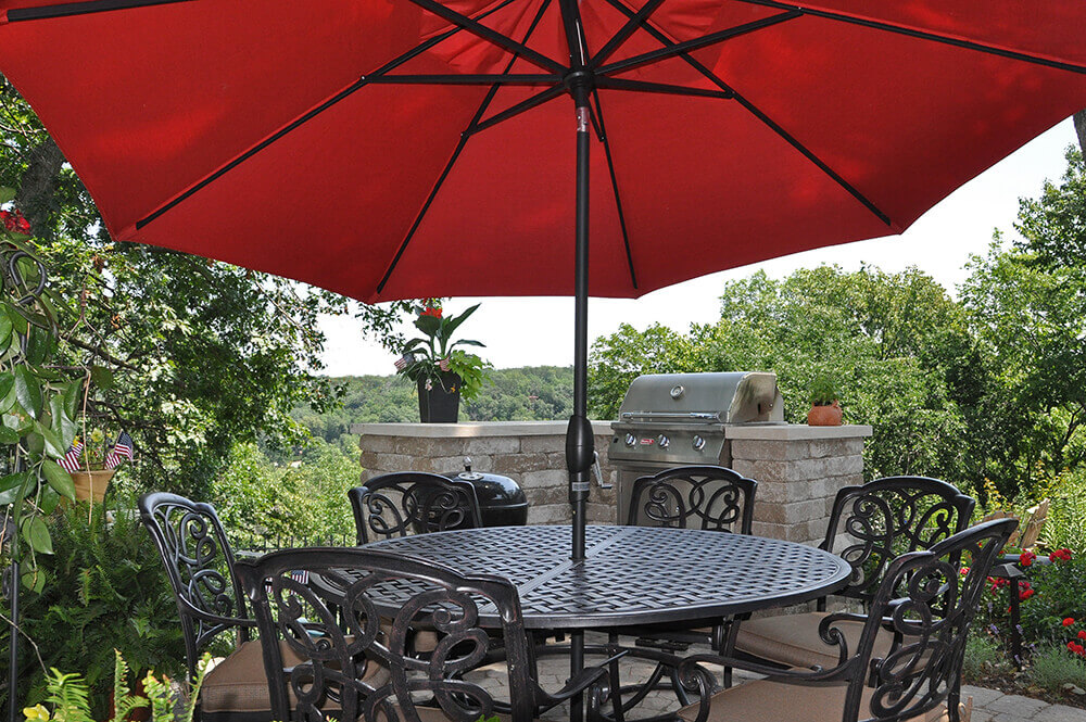 Large red umbrella covering table with built-in grill area.