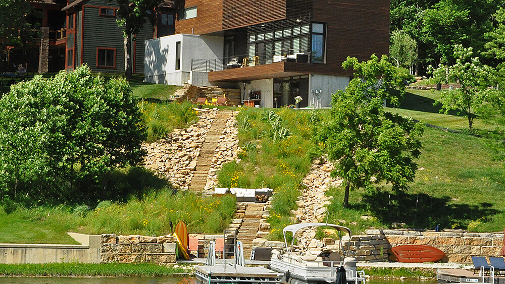 Residential landscape design with stone stairs and greenery.