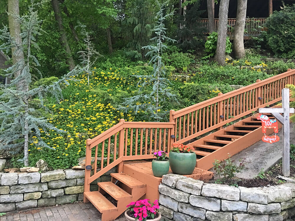 Residential landscape design with stairs and rock retaining wall.