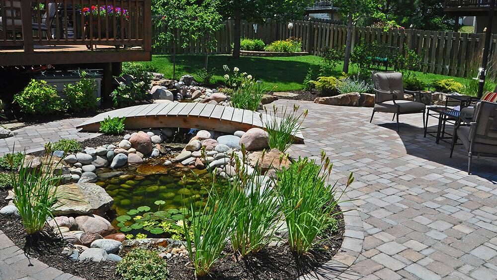 Paved backyard area with small pond and bridge.