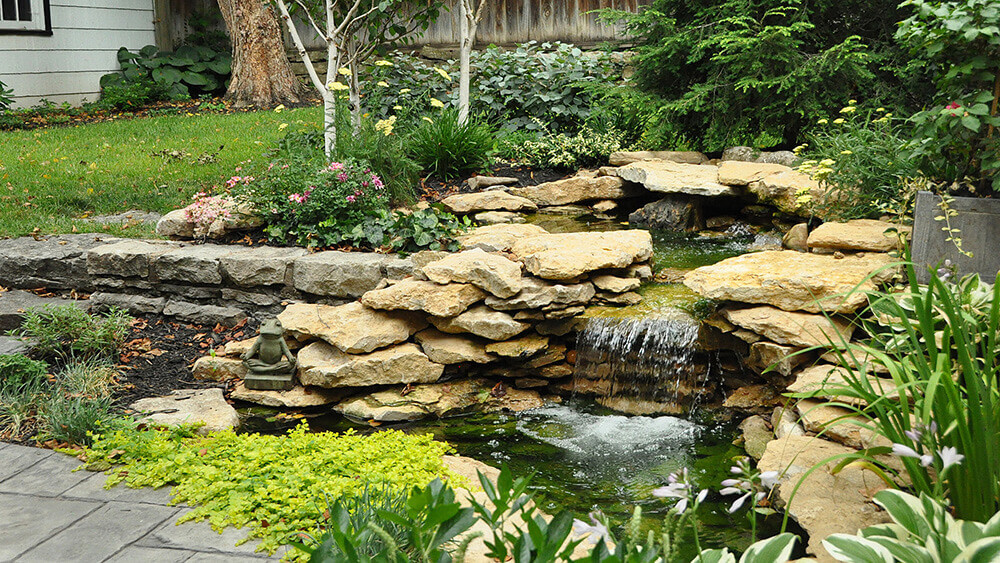 Limestone rock wall and water fall in residential landscape design.