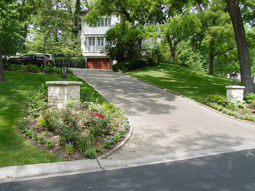 Residential landscape design with paved driveway and pillars.