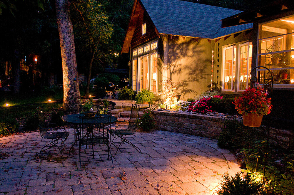 Backyard with tables and chairs at night.