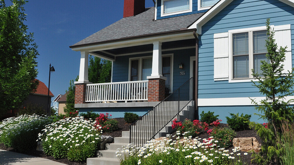 Front of home with concrete steps and railing, surrounded by white flowers.