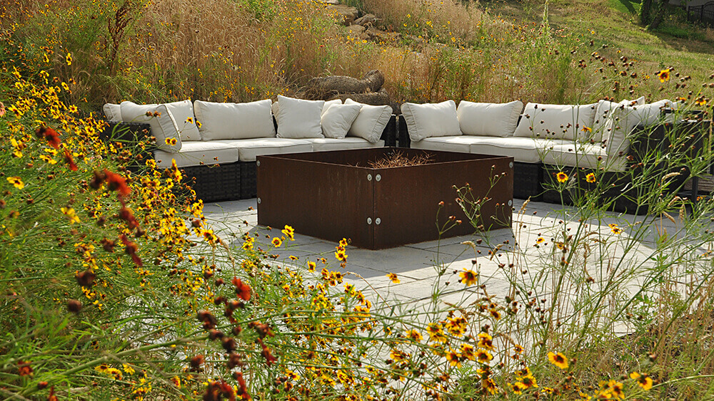 fire pit with seating area surrounded by yellow flowers