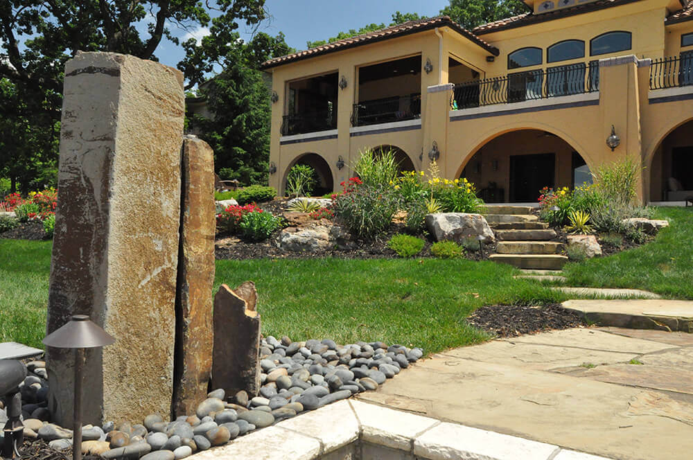 Residential landscape design with rocks and bright flowers.
