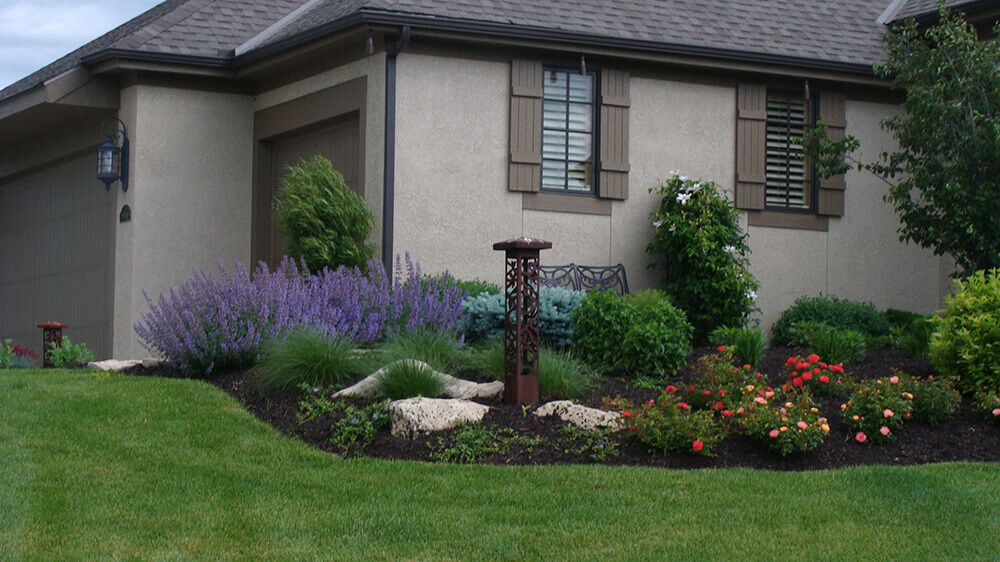 Residential landscape design with bright flowers in front of house.