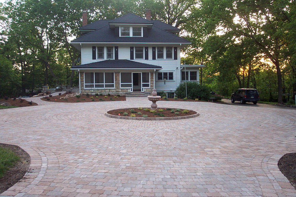 Residential landscape design with paved driveway and statue.