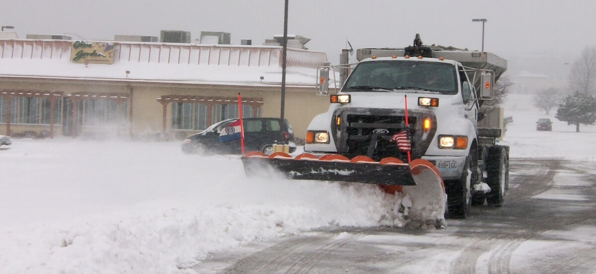 Truck plows snow to remove from roads.