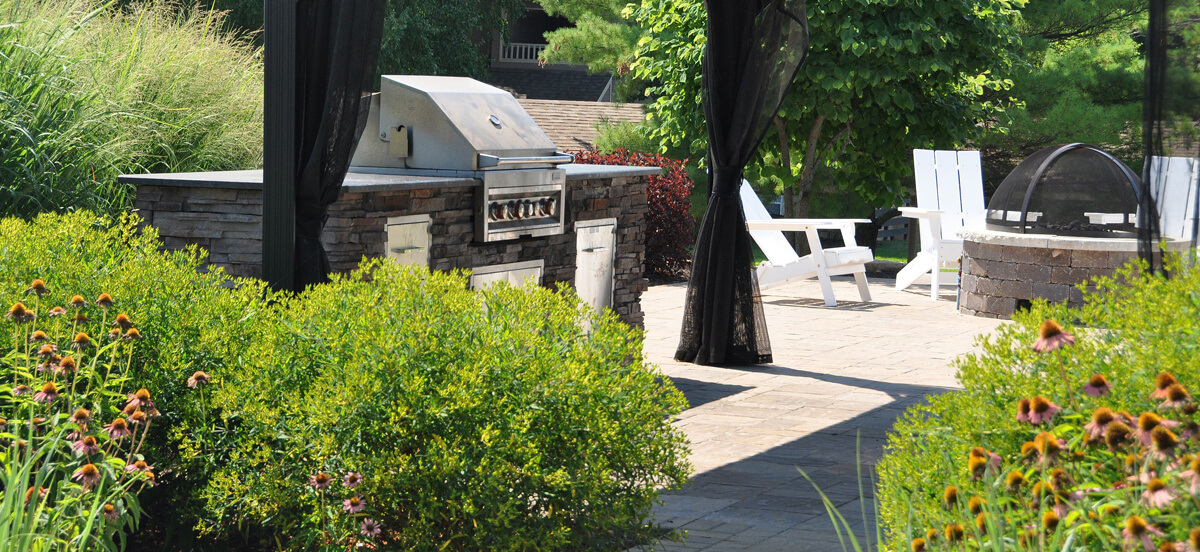 Landscape design with grill and firepit, completed by Embassy Landscape Group.
